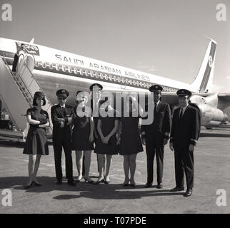 1960s, Saudian Arabian Airlines crew line-up outside their plane. - Stock Image
