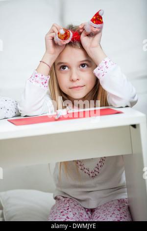 Thoughtful Girl Holding Santa Headband - Stock Image