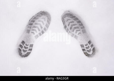 two shoe prints on snow, top view, copy space, cloudy, no sunshine - Stock Image