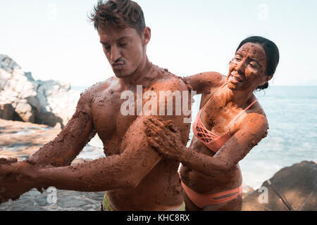 Two people helping each other to apply mud to their naked skin as part of a cleaning process. - Stock Image