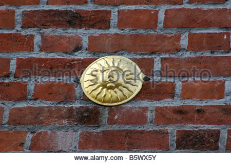 Sun firemark showing that the owner of the building had bought insurance with that company. - Stock Image