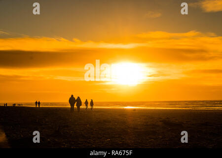 Ynyslas  Wales UK, 01/01/2019 UK Weather: People walking along the sandy beach at Ynyslas, near Aberystwyth, west Wales, as the sun sets at the end of the first day of the 2019 new year  photo credit: Keith Morris / Alamy Live News - Stock Image