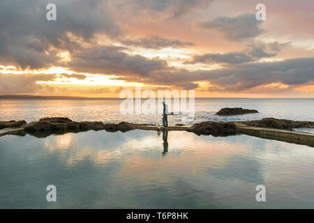 Mousehole, Cornwall, UK. 2nd May 2019. UK Weather. Mild, calm and cloudy at sunrise for this early morning dog walker at Mousehole. Credit Simon Maycock / Alamy Live News. - Stock Image