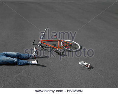 Legs of bike rider with crashed bicycle on asphalt. - Stock Image