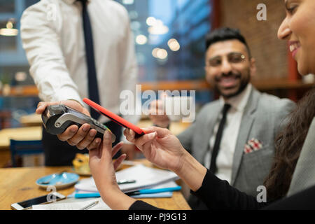 Businesswoman paying with smart phone contactless payment in cafe - Stock Image
