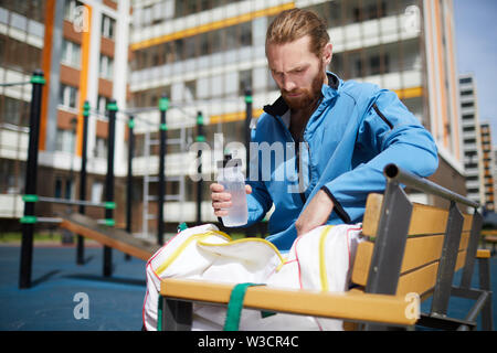 Serious bearded guy in blue jacket sitting on bench and getting water bottle out of bag while taking break on outdoor sports ground - Stock Image