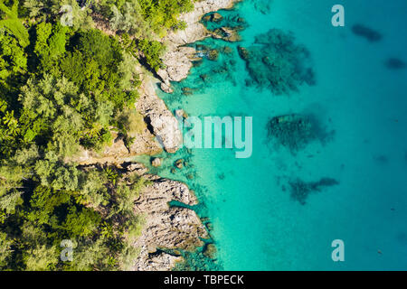 View from above, stunning aerial view of a tropical coast bathed by a turquoise clear sea. Phuket, Thailand. - Stock Image