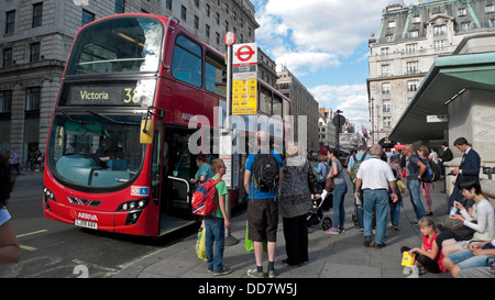 People standing at a bus stop and passengers boarding a Victoria 38 bus at Green Park  London England UK  KATHY - Stock Image