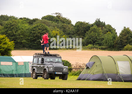 A couple trying to get a phone signal on the roof of their Landrover on a campsite in Cley on the North Norfolk coast, UK. - Stock Image
