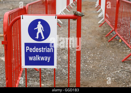 Pedestrian walkway sign and barriers on a UK construction site - Stock Image