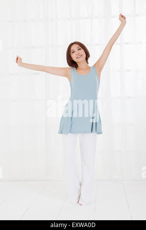Young woman standing with arms outstretched, - Stock Image