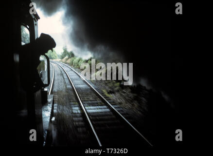 Train on private line leaving tunnel with smoke. England 1990 - Stock Image