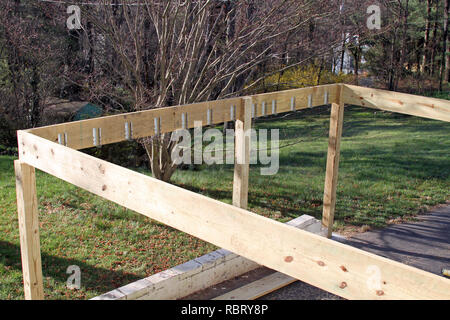 Building construction frame of a house's new exterior wood deck being built in Springtime - Stock Image