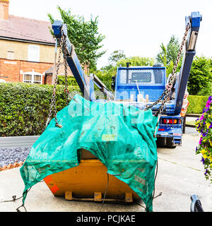 Skip Hire, Collecting skip, refuge collection, skip lorry, skip collection, full skip, skip loader, waste collection, collecting rubbish, skip, hire, - Stock Image