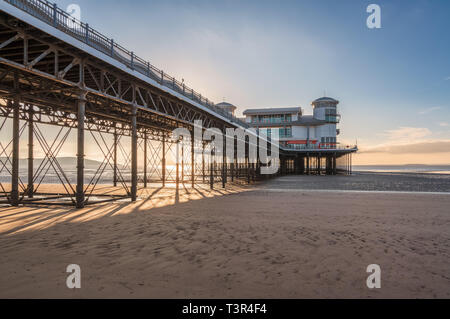 Weston-super-Mare, North Somerset, England, UK - October 04, 2018: The setting sun over the beach and the Grand Pier - Stock Image