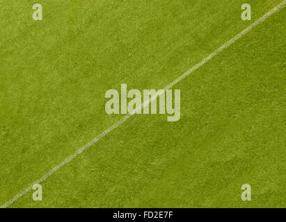 A white line diagonally dividing a grass playing surface - Stock Image