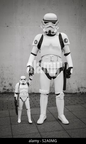 A male cosplayer dressed as a Stormtrooper from the Star Wars movies holding the hand of a small child also in a costume - Stock Image