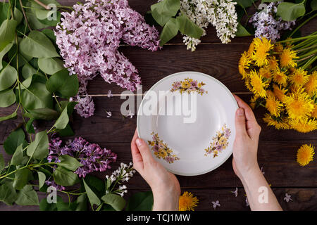 Plate and decor of flowers on the background of vintage wooden planks. Vintage background with flowers of dandelion and lilac and a place under the te - Stock Image