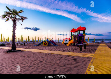 Playground for children on the beach with pavement and a palm at sunrise. Jesolo, Italy. - Stock Image