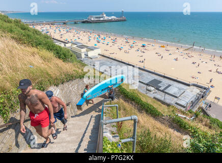 Bournemouth, UK. 6th July 2018. UK Weather, a man carries a surfboard up steps as thousands of tourists hit the beach in Bournemouth as the summer 2018 heatwave continues. Credit: Thomas Faull / Alamy Live News - Stock Image