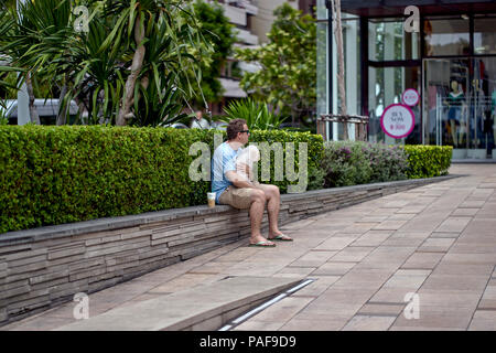 Man caring for a dog whilst his wife is shopping nearby - Stock Image
