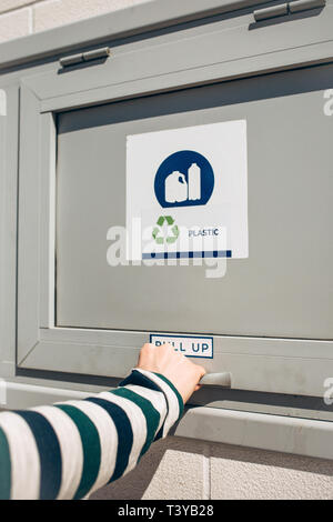 A person opens or closes a modern waste bin for separate collection of waste. - Stock Image