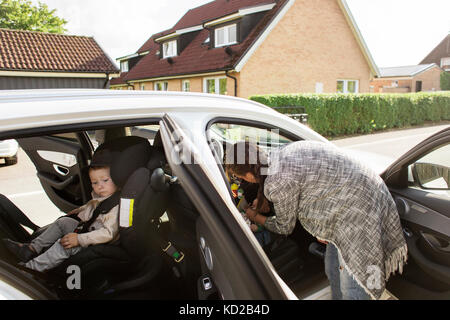 Mother fastening son's (18-23 months, 0-1 months) seat belt - Stock Image