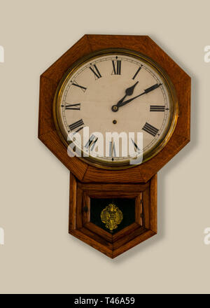 Eight corners wooden vintage clock on tan wall - octagon - Stock Image