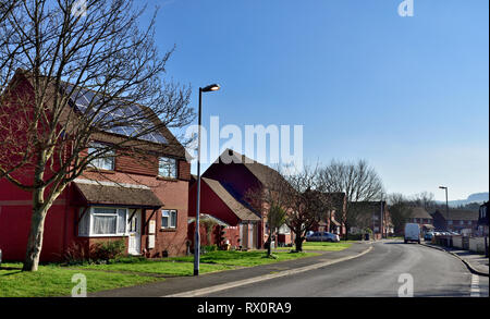 Row of modern two story houses in Tiverton, Devon with open gable roofs, one with solar panels - Stock Image