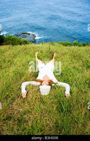 Young woman relaxing in grass near ocean in Maui Hawaii - Stock Image