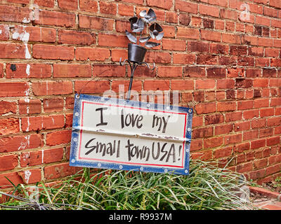 I Love My Small Town sign displayed against a brick wall in Warm Springs Georgia, USA. - Stock Image