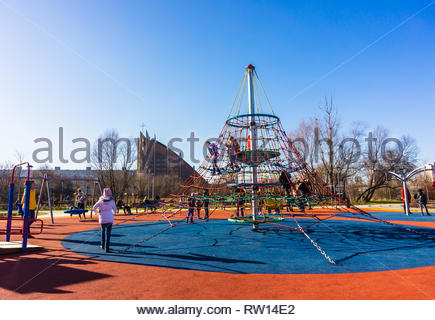 Poznan, Poland - February 16, 2019: Children at a new build playground with different equipment including a climb rope net in the Rataje park on a sun - Stock Image