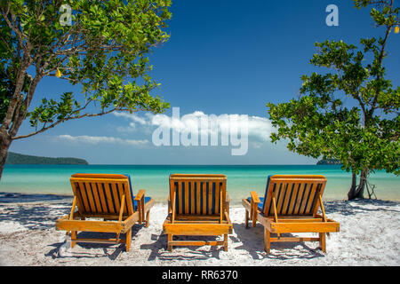 Three luxury wooden sun loungers in a line on a white sand paradise island beach with turquoise sea. - Stock Image
