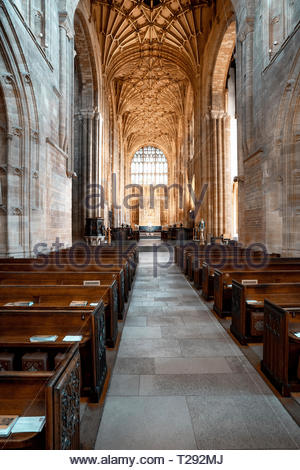 Looking toward the altar between pews at Sherborne Abbey UK - Stock Image