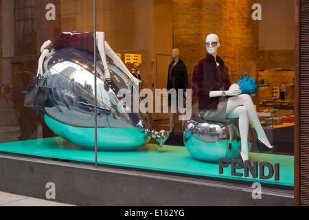 Manhattan, New York, U.S. - May 21, 2014 - In the Fendi 5th Avenue store window display, mannequins wearing brown dresses and shoes are sitting on, and in supine position lying on, large structures resembling silver Mylar balloons, NYC. A brown leather Fendi purse hangs from one hand. - Stock Image