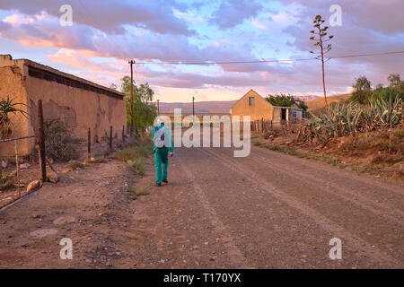 Karoo dirt road leading to a bend in morning light. Man in green overall by farm house seen from back walking to work - Stock Image