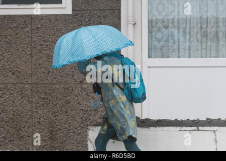 Woman walking in rain carrying blue umbrella and wearing blue backpack. In front of building and window - Stock Image