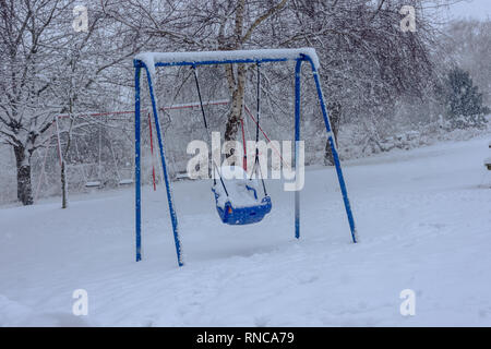 Blue childrens swing for the disabled in a snowy playground - Stock Image