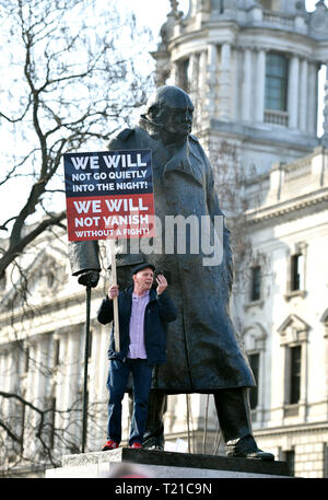 London, UK. 29th Mar, 2019. A Pro Brexit supporter climbs up on the Churchill statue at the Brexiteers Rally in Parliament Square London today as they show their anger at not leaving the EU today causing traffic chaos in the city . MP's are sitting today to debate leaving the European Parliament on the day it was originally supposed to happen Credit: Simon Dack/Alamy Live News - Stock Image