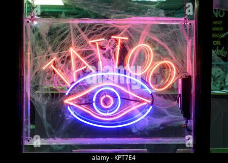 Orange and purple tattoo neon advertising sign in Halloween cobwebs - Stock Image