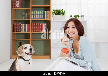 Young woman sitting with her dog and holing an apple with smile, - Stock Image