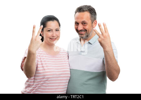 Smiling couple showing two and three numbers with fingers as counting concept isolated on white background - Stock Image