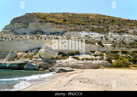 Surrounding the beautiful resort town of Agua Amarga in the Cabo de Gata Natural Park (Spain) are fantastic sea cliffs with caves carved into the rock. - Stock Image