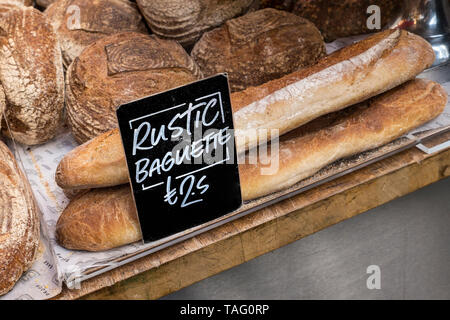 Rustic authentic fresh Baguettes on display at Borough Market Bakery. Speciality bread Borough Market Bakery 'Bread Ahead' stall inside with variety of attractive hand made artisan breads on display for sale. Artisan speciality bakery stall at Borough Market Southwark London UK - Stock Image