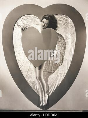 Hiding behind her heart - Stock Image