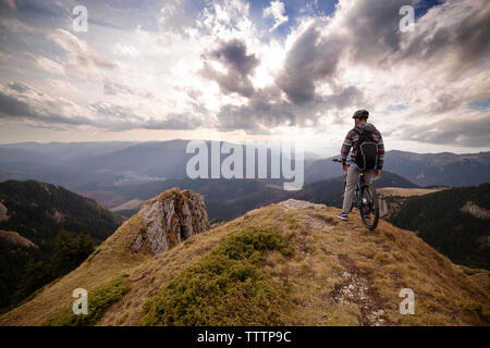 Rear view of man on bicycle on mountain against cloudy sky - Stock Image