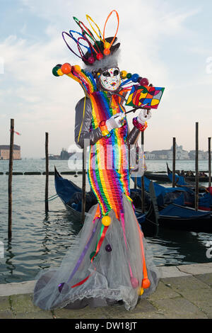 Venice, Italy. 25th Feb, 2014. A dramatic rainbow dress features in this art inspired costume posed in front of gondolas at Venice Carnivale - Tuesday 25th February. Credit:  MeonStock/Alamy Live News - Stock Image