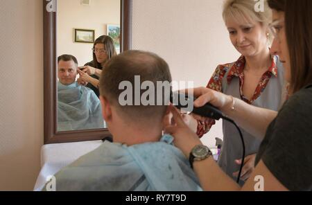 International Space Station Expedition 59 crew member Nick Hague of NASA has his hair cut by a stylist as fellow crew member, Christina Koch of NASA, assists at the Baikonur Cosmodrome March 12, 2019 in Baikonur, Kazakhstan. Expedition 59 crew: Christina Koch of NASA, Alexey Ovchinin of Roscosmos, and Nick Hague of NASA will launch March 14th onboard the Soyuz MS-12 spacecraft for a six-and-a-half month mission on the International Space Station. - Stock Image