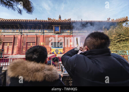 People burning incenses in Yonghe Temple also called Lama Temple of the Gelug school of Tibetan Buddhism in Dongcheng District, Beijing, China - Stock Image