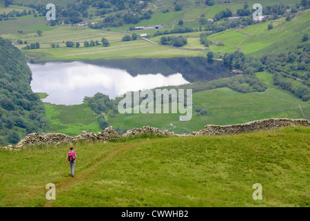 A hiker descending High Hartsop Dodd with Brothers Water and Hartsop in the distance. Lake District. - Stock Image